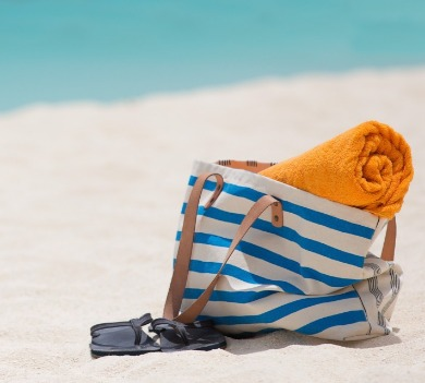 blue striped beach bag with orange towel and flip-flops on beach | Coastline Realty Vacations