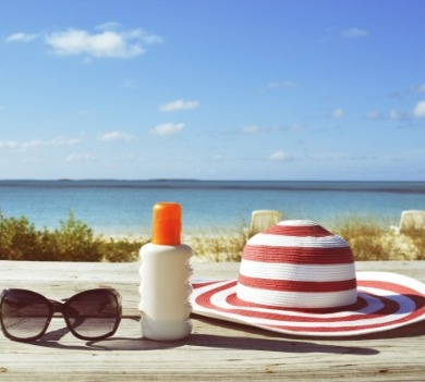 red striped hat, sunglasses and sunscreen on beach | Coastline Realty Vacations