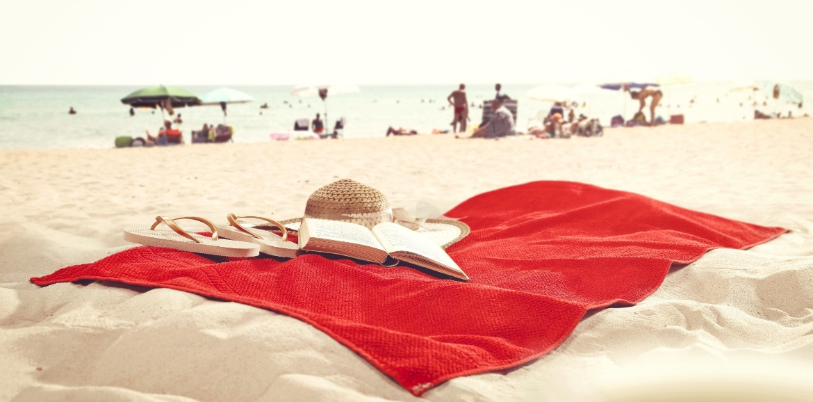 red towel with book, flip flops and beach hat on beach | Coastline Realty Vacations