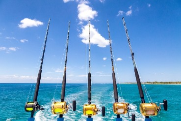 fishing reels off the back of a boat offshore fishing | Coastline Realty
