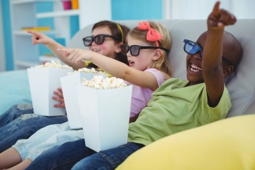 three children watching a movie and eating popcorn | Coastline Realty