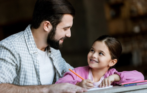 father and daughter writing note to put in time capsule | Coastline Realty