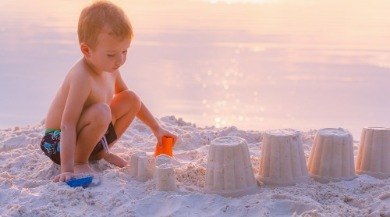 boy building a sand castle on the beach | Coastline Realty Vacations