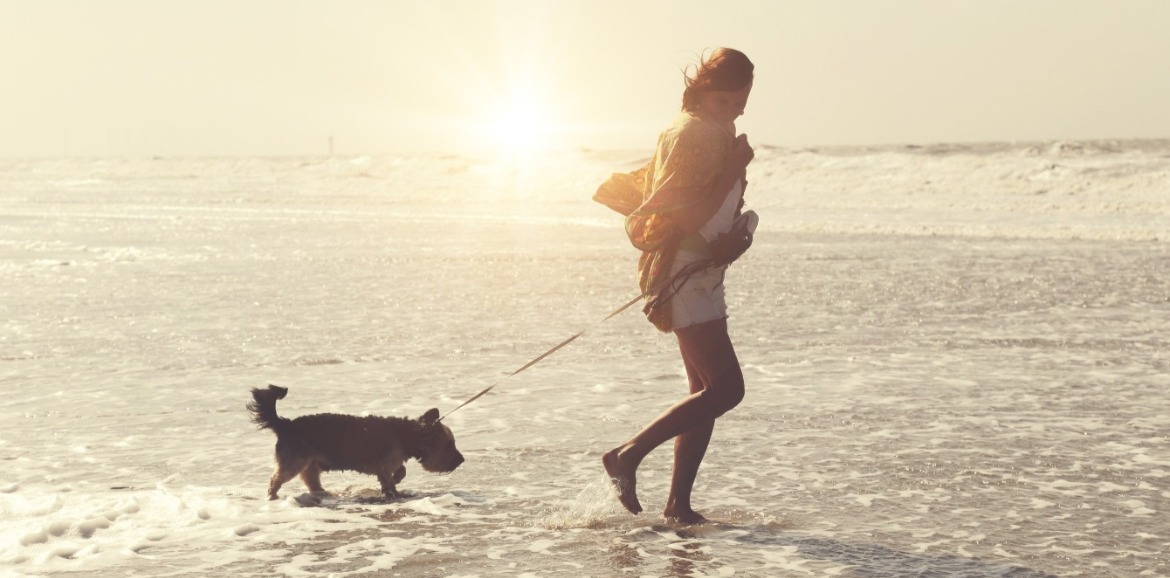 woman and dog on topsail beach | Coastline Realty Vacations