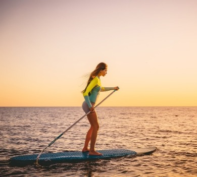 woman paddleboarding on topsail island | Coastline Realty Vacations