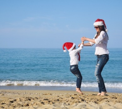 mother and daughter in santa hats at the beach | Coastline Realty Vacations