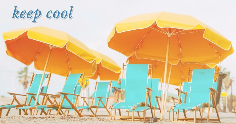 yellow beach umbrellas over teal chairs on the beach | Coastline Realty Vacations