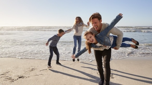 family enjoying the beach during Fall | Coastline Realty
