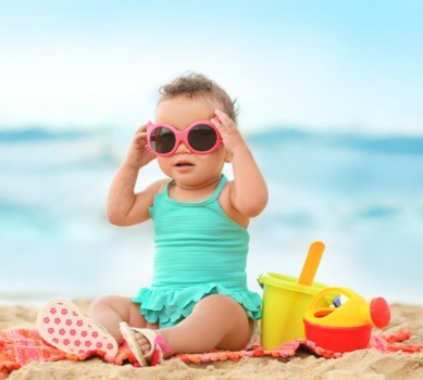 baby girl wearing sunglasses on the beach | Coastline Realty