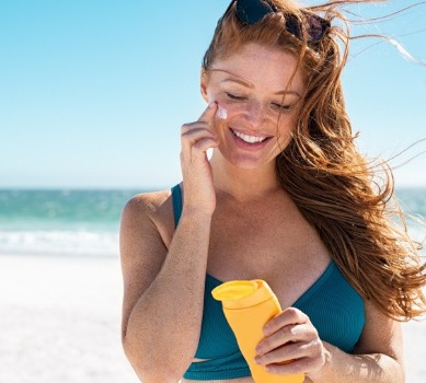 woman applying sunscreen on the beach | Coastline Realty
