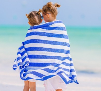 little girls wrapped up in beach towel on the beach | Coastline Realty