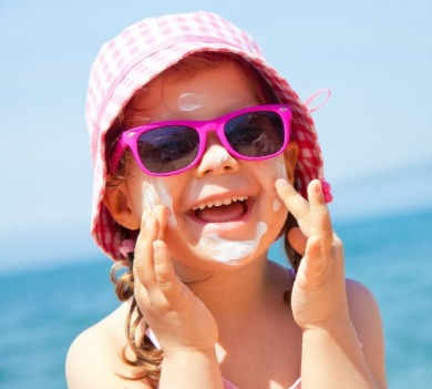 little girl wearing sun hat, sunglasses, and sunscreen on the beach | Coastline Realty