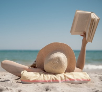 woman laying on the beach reading a book | Coastline Realty