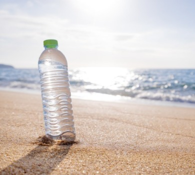 water bottle sitting in the sand on the beach | Coastline Realty
