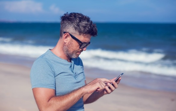 man using cell phone on the beach | Coastline Realty