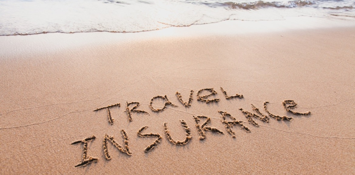 travel insurance written in the sand on the beach | coastline realty