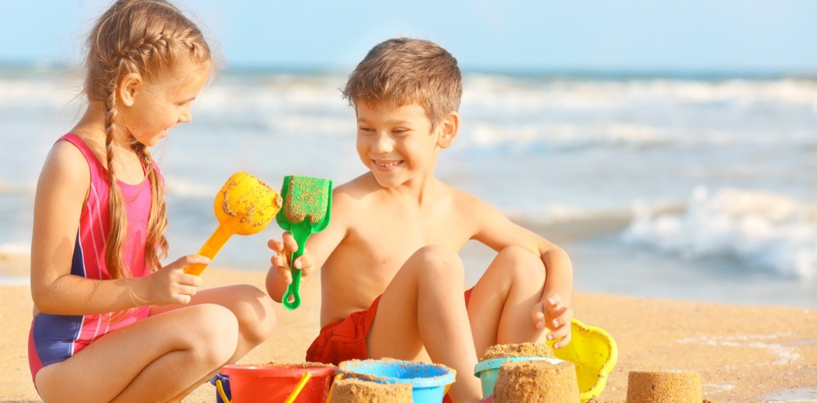 kids playing on the beach with toys | coastline realty